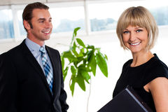 Handsome boss passing by smiling female colleague Royalty Free Stock Images