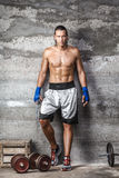 Handsome boxer man standing on the wall and looking at camera. Portrait of handsome boxer man standing on the wall and looking at camera with intense gaze Stock Image