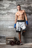 Handsome boxer man standing on the wall. Portrait of handsome boxer man standing on the wall and looking at camera with intense gaze Royalty Free Stock Photo
