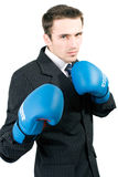 Handsome boxing man in suit isolated. Handsome young man in suit and gloves boxing in office, made in studio isolated on white background Stock Photos