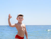 Handsome Boy at the Beach Showing Okay Hand Sign Royalty Free Stock Image