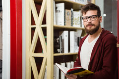 Handsome boy with beard in glasses reading book Stock Photography