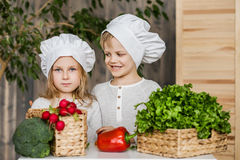 Handsome boy and beautiful young girl playing in the kitchen chefs. Healthy food. Vegetables Royalty Free Stock Images