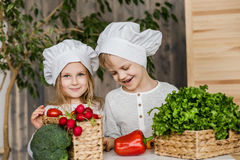 Handsome boy and beautiful young girl playing in the kitchen chefs. Healthy food. Vegetables Stock Images