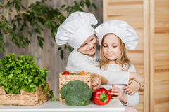 Handsome boy and beautiful young girl playing in the kitchen chefs. Healthy food. Vegetables Royalty Free Stock Image