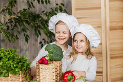 Handsome boy and beautiful young girl playing in the kitchen chefs. Healthy food. Vegetables Royalty Free Stock Photo