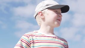 Handsome boy blond in a cap on his head against the sky. Close-up of a child`s face. The boy smiles and talks about something stock footage