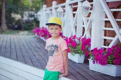 Handsome boy with blond hairs wearing pink t-shirt green pants and yellow cap posing in city down town central park close to flowe. Rs baskets on wooden floor Royalty Free Stock Images