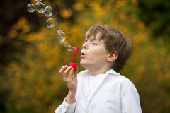 Handsome boy blowing soap bubbles Royalty Free Stock Photography