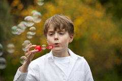 Handsome boy blowing soap bubbles Stock Photos