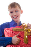 Handsome boy in a blue shirt stands with a gift Royalty Free Stock Photography
