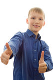 Handsome boy in a blue shirt stands and smiles Royalty Free Stock Photos