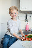 Handsome boy is cooking in the kitchen at home. Healthy food Stock Image