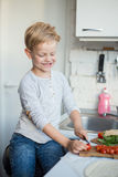 Handsome boy is cooking in the kitchen at home. Healthy food Royalty Free Stock Image