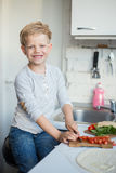 Handsome boy is cooking in the kitchen at home. Healthy food Royalty Free Stock Images