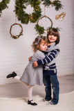 Handsome boy and cute small girl on Christmas background Royalty Free Stock Photo