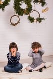 Handsome boy and cute small girl on Christmas background Royalty Free Stock Photos