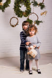 Handsome boy and cute small girl on Christmas background Stock Images