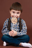 Handsome boy eating lollipop sitting on the floor Stock Photo