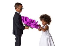 Handsome boy gives a cute girl big origami flower.Kids love.Isolated. Over white background stock images