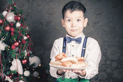 Handsome boy giving to Santa Claus cookies at Christmas Stock Photos