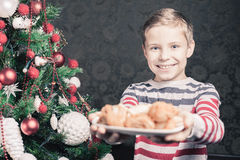 Handsome boy giving to Santa Claus cookies at Christmas Royalty Free Stock Photo