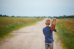 Handsome boy with guitar walking on the road in summer day. Back view Royalty Free Stock Photography