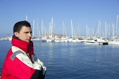 Handsome boy on harbor with red marine coat Royalty Free Stock Image