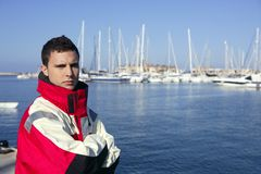 Handsome boy on harbor with red marine coat. Handsome boy on blue marina harbor with red marine coat Stock Photography