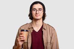 Handsome boy has curly hair, beard wears round transparent glasses, holds coffee to go, has break, communicates with friends, mode. Ls against white background stock photography