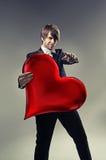 Handsome boy holding a cartoon heart Stock Photos