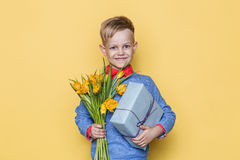 Handsome boy holding flower bunch and gift box. Valentine`s day. Birthday. Mother`s day. Studio portrait over yellow background Royalty Free Stock Photo