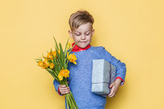 Handsome boy holding flower bunch and gift box. Valentine`s day. Birthday. Mother`s day. Studio portrait over yellow background Stock Photography