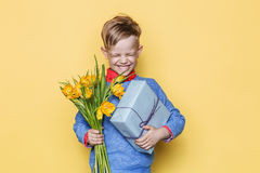 Handsome boy holding flower bunch and gift box. Valentine`s day. Birthday. Mother`s day. Studio portrait over yellow background Royalty Free Stock Image
