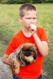 A handsome boy is holding his friend, a yellow dog of the Pekingese breed.  He looks thoughtfully with his hand over his mouth. A handsome boy is holding his Royalty Free Stock Photos