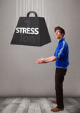 Handsome boy holding one ton of stress weight Royalty Free Stock Images