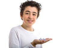 Handsome boy holds some dice in the palm of hand. Handsome boy isolated on white background holds some dice in the palm of his right hand smiling with happy eyes Royalty Free Stock Photo