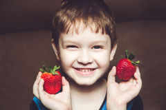 Handsome boy holds a strawberry Royalty Free Stock Photos