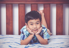 Handsome boy lying barefoot on bed in bedroom. Happy child smili Stock Image