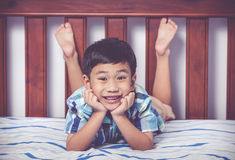 Handsome boy lying barefoot on bed in bedroom. Happy child smili Royalty Free Stock Photography