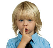 Handsome boy making a be quite sign on white. Cute, well dressed boy putting finger to lips and making a be quiet sign. Isolated on white Royalty Free Stock Photos