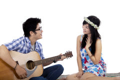 Handsome boy plays guitar to his girlfriend Royalty Free Stock Image