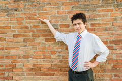Handsome boy presenting in front of a brick wall Royalty Free Stock Photos
