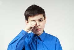 Handsome boy rubs his eyes. On the background Royalty Free Stock Photos