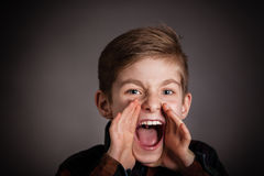 Handsome Boy Screaming at the Camera Against Gray Royalty Free Stock Photo