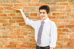 Handsome boy showing in front of a brick wall Royalty Free Stock Photo