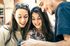 Handsome Boy shows Pictures to beautiful Girls. Portrait of handsome young men showing photos in the digital camera to beautiful surprised girls Stock Photos