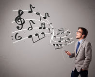 Handsome boy singing and listening to music with musical notes Royalty Free Stock Photos