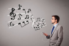 Handsome boy singing and listening to music with musical notes Royalty Free Stock Images