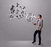 Handsome boy singing and listening to music with musical notes Royalty Free Stock Photo